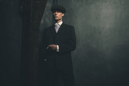 blinders: Retro 1920s english gangster standing with cigarette. Wearing suit and flat cap. Stock Photo