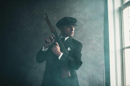 distinctive: Retro 1920s english gangster wearing flat cap and suit. Standing with gun looking out window. Stock Photo