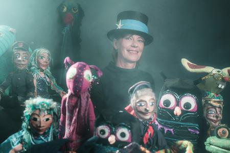 Mystical puppeteer standing between handmade puppets.