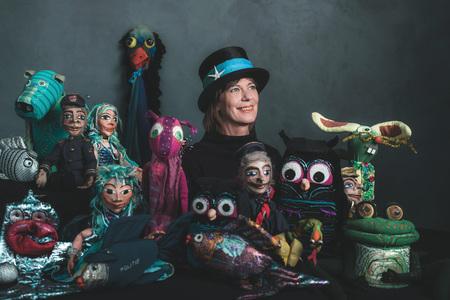 Smiling puppeteer standing between handmade puppets. Stock Photo
