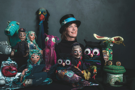 puppet master: Smiling puppeteer standing between handmade puppets. Stock Photo