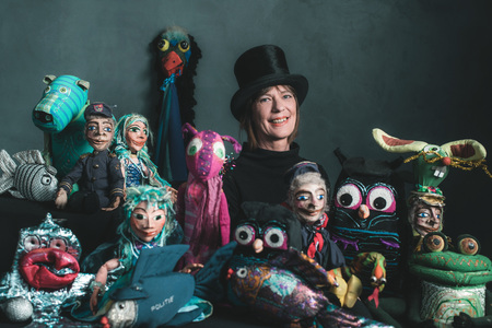 Sourire marionnettiste debout entre les marionnettes faites à la main.