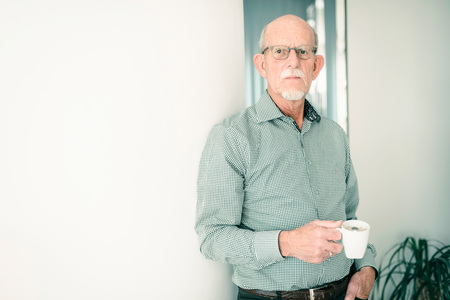 leaning against: Senior man having coffee break at home. Stock Photo