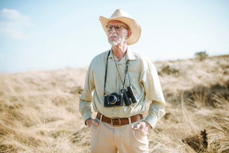 Senior safari man with camera and binocular in field.
