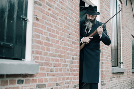 Man with long beard dark dressed standing with rifle ready to shoot. Stock Photo