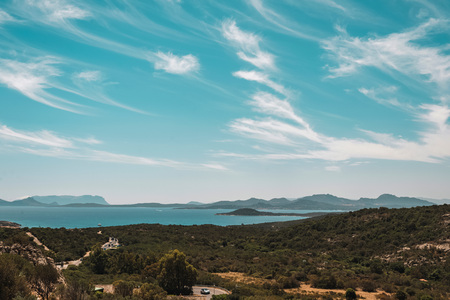 Summer mountain landscape with lake and road far away under blue cloudy sky. Sardinia. Italy. Stock Photo