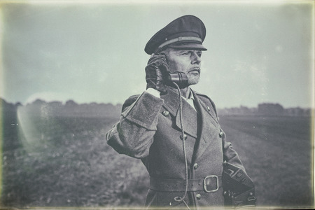 Antique black and white photo of 1940s military officer calling with field phone while standing on farmland. Stock Photo