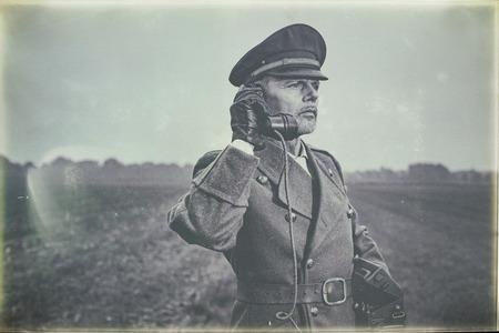 Photo en noir et blanc antique d'un officier militaire des années 1940 qui appelle avec un téléphone de terrain tout en restant sur les terres agricoles.
