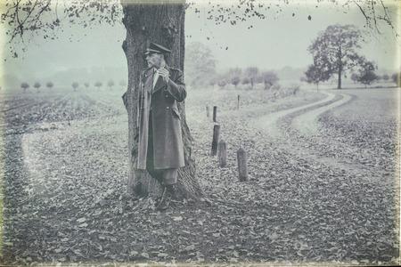 Photo antique en noir et blanc de l'officier militaire des années 1940 qui se repose fumant de la cigarette sous l'arbre. Banque d'images