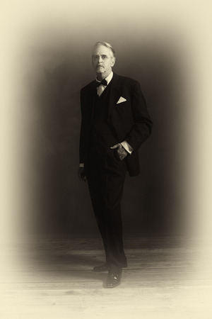 Antique plate photo of middle aged vintage 1920s businessman in black suit with bow tie.