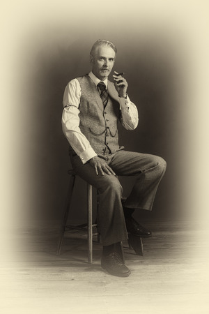 Antique plate photo of middle aged vintage 1920s man wearing suit with cigar sitting on wooden stool. Stock Photo
