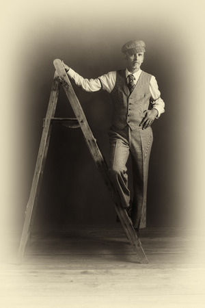 Antique plate photo of vintage 1920s man in suit standing on old wooden ladder. Stock Photo