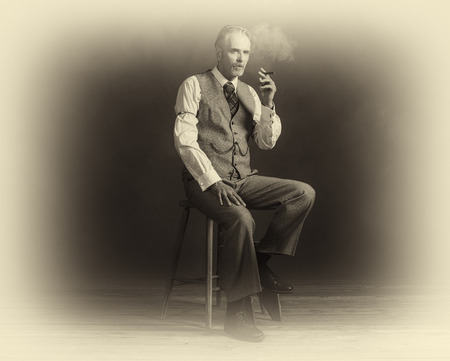 Antique plate photo of cigar smoking vintage 1920s man wearing suit sitting on wooden stool. Stock Photo