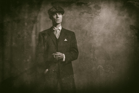 blinders: Antique wet plate photo of 1920s english gangster standing with cigarette.
