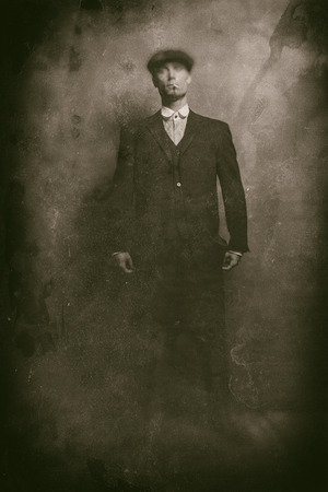 blinders: Antique wet plate photo of 1920s english gangster smoking a cigarette. Wearing suit and flat cap.