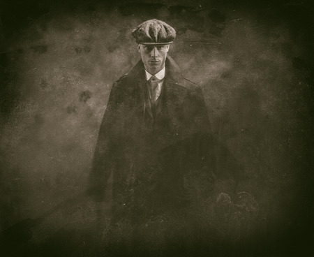 blinders: Antique wet plate photo of threatening 1920s english gangster holding gun in smoky room. Stock Photo