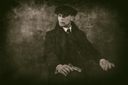 blinders: Retro 1920s english gangster with gun sitting on chair. Peaky blinders style.
