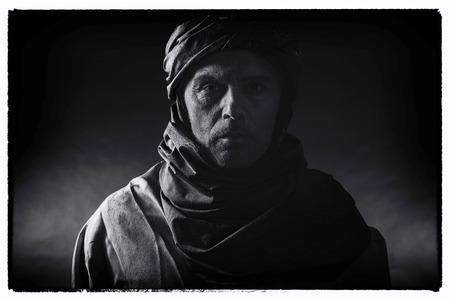 Vintage black and white photo of berber man in night light wearing turban with robe. Studio shot.