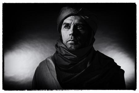 Foto blanco y negro del vintage del hombre del berber en turbante que desgasta de la luz de la noche con el traje. Tiro del estudio. Foto de archivo - 82411110