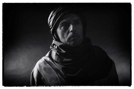 Foto blanco y negro del vintage del hombre del berber en turbante que desgasta de la luz de la noche con el traje. Tiro del estudio. Foto de archivo - 82411131