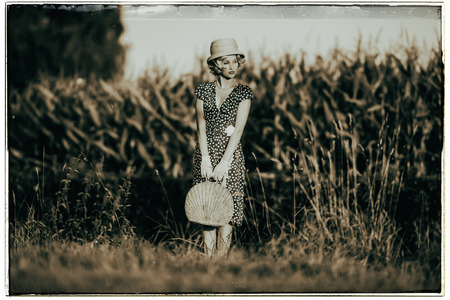 Classic black and white photo of 1920s summer fashion woman with dress and straw hat standing with handbag in rural landscape.