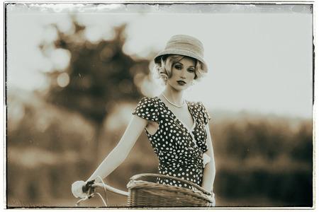 vestidos de epoca: Foto blanco y negro clásica de la mujer de la moda de los años 30 en alineada del vestido del verano con la bicicleta en paisaje rural.