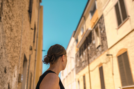 Rear view of brunette woman looking in street of old italian town. Sardinia. Italy.