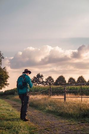 vanishing point: Man with backpack and hat on rural path.