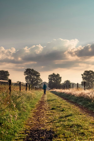 vanishing point: Man in hat walking alone on end of rural track.