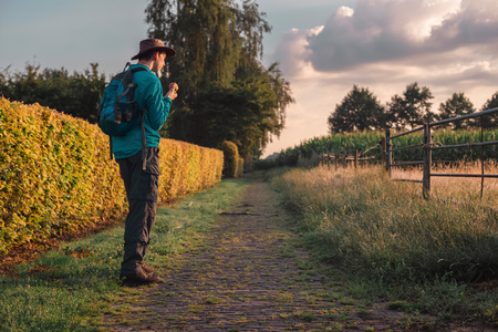 Man with backpack and hat on rural path.