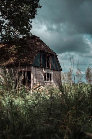 Neglected farmhouse in wild garden under dark cloudy sky. Stock Photo