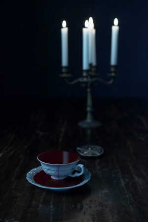 White tea cup in dark blood on dark wooden table with burning candles in candleholder.