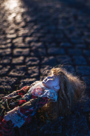 Vintage china doll lying in cobblestone street backlit by low autumn sunlight.