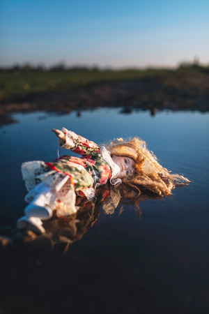 China doll lying in puddle in countryside. Low angle view.