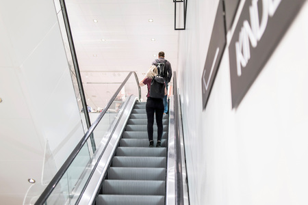 Young woman and man on escalator in store.