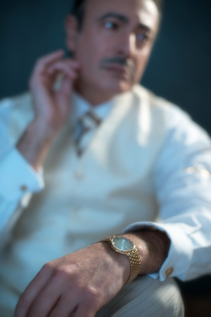 Vintage 1920s business man with mustache and golden watch.