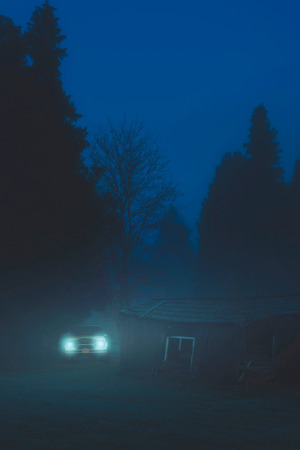 Off road car with headlights on in misty forest near old barn at dusk. Stock Photo