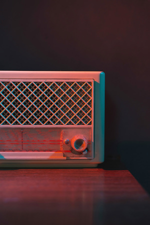 Vintage transistor radio on wooden table in colored light.