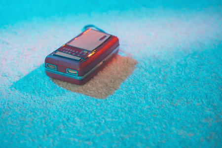 Portable vintage transistor lying on white carpet lit by colored light.