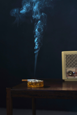 Ashtray with burning cigarette and transistor radio on vintage wooden table at night.