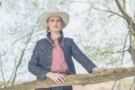 Retro 1950s cowgirl standing at wooden fence in countryside.