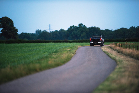 Pickup truck driving on country road in evening. Stock Photo