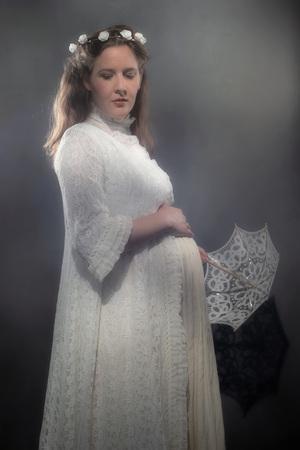 Historical pregnant brunette woman in white dress holding umbrella.