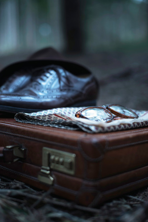 Abandoned briefcase with shoes, hat, glasses and shawl in forest.