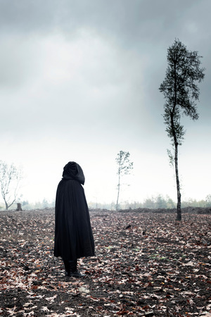 Woman in black cape in moody landscape.