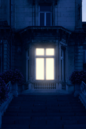 Illuminated window of historical mansion.