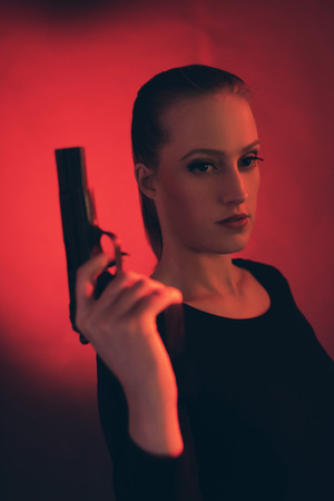 Blonde woman with pistol against red background.