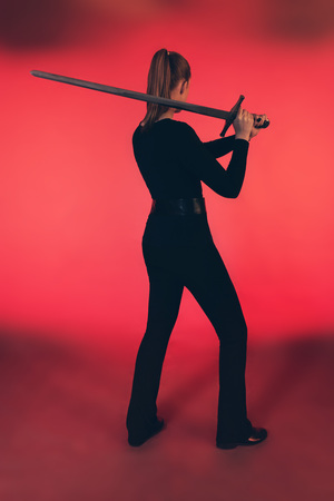 Woman standing with sword against red background.