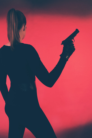 Woman with gun against red backround.