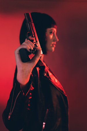 Woman with gun dressed in black against red background.